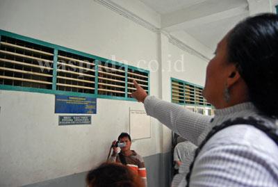 Salah seorang keluarga dari tahanan kasus Protap memberikan semangat melalui celah jendela ruang tahanan Pengadilan Negeri Medan, Kamis (16/7).Dia meminta, seluruh tahanan berdoa, agar Tuhan memberkati mereka semua.