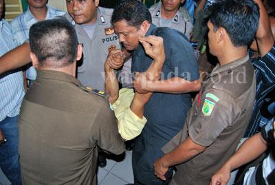 Salah seorang terdakwa kasus Protap yang pingsan dibawa keluar dari ruang tahanan Pengadilan Negeri (PN), menuju ruang Poliklinik PN Medan, Kamis (16/7). Diduga kedua terdakwa yang pingsan tersebut akibat pukulan dari pihak pengamanan PN medan yang mengamankan kericuhan di dalam ruang tahanan tersebut.