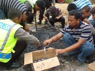 Polisi saat mengumpulkan puing-puing kebakaran dan tulang-belulang Dina br Situmeang (72) dan anaknya Tigor Manik (49)